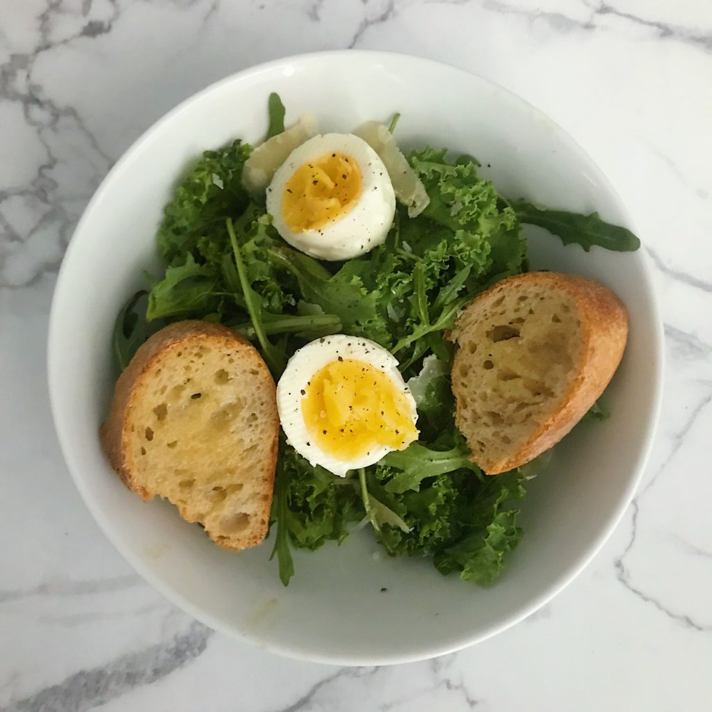 breakfast salad with arugula, kale, soft-boiled egg, bageutte