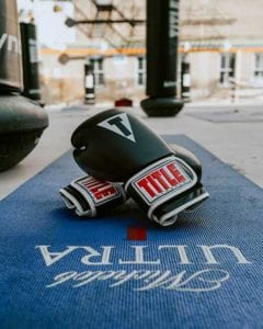 Title Boxing - gloves on floor with boxing bags